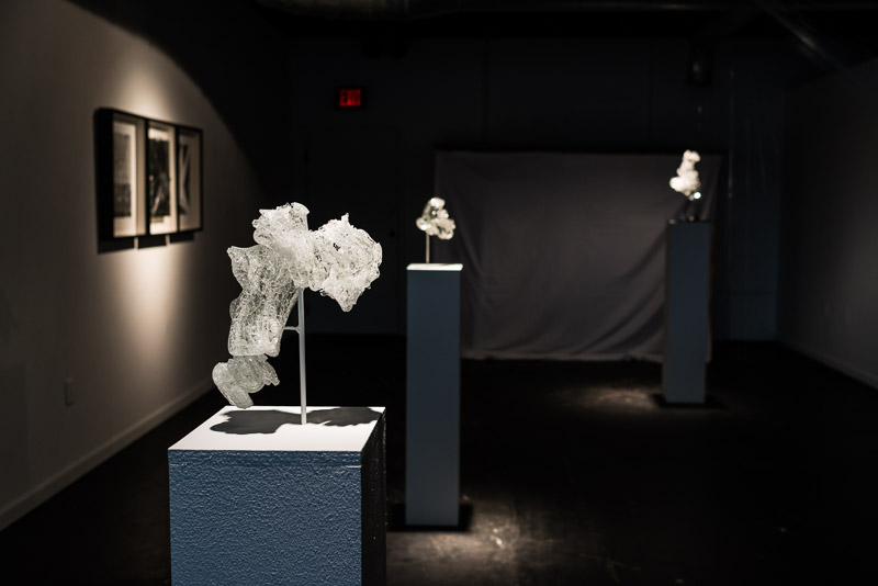 Installation view of Mesophase.  Glass into Water 2 (foreground); Reflect on the Broken 2 (triptych, left); Glass into Water 1 (center); Glass into water - Plunge 1 (right). Photo by Alisa Levy