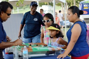 A family learns about water management at one of the dozens of booths at Turn Up! this past Saturday. Children can earn digital badges at each booth after finishing a learning activity. Badges can be used as a portfolio of the children's accomplishments. Photo by Christina Ulsh.