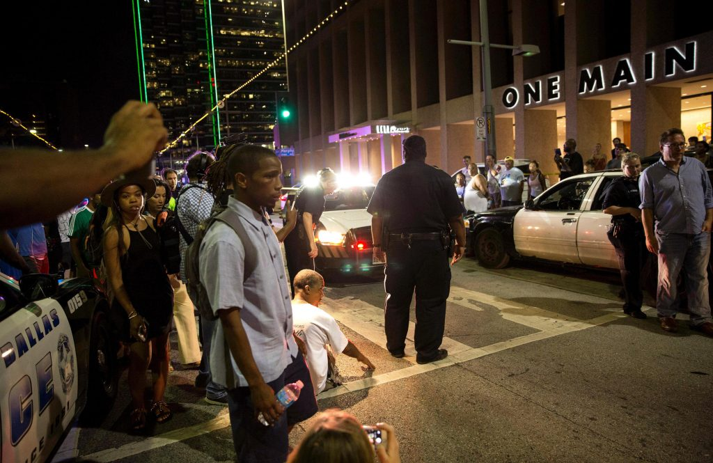 Police attempt to calm the crowd as someone is arrested near the scene of the sniper shooting in Dallas. Photo:LAURA BUCKMAN / AFP/GETTY IMAGES